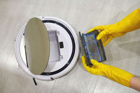 Dust storage box case of robotic vacuum cleaner in gloved female hands. Woman in protective gloves taking out container and filter to clean it from dirt and debris. Vacuum cleaning concept, close up.