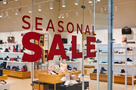 Sale time in footwear store at european shopping center. Christmas promotions in shop. Seasonal sale, holiday discounts in shopping mall.
