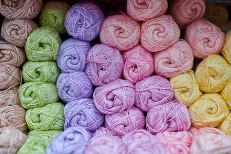 Yarns or balls of wool on shelves in store for knitting and needlework, close up. Accessories for haberdashery in fabric store shelves. Multicolored picture, background.