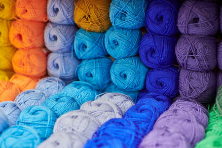 Yarns or balls of wool on shelves in store for knitting and needlework, close up. Accessories for haberdashery in fabric store shelves. Multicolored picture, background. 免版税图像