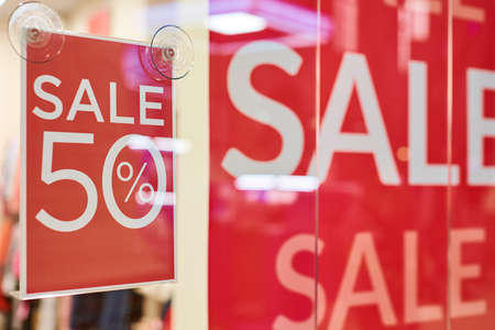 Seasonal super sale 50% off, holiday discount in shopping mall. New Year's sale time at european shopping center. Black Friday. Christmas promotions in clothing store.
