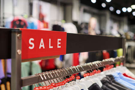 Seasonal sale, holiday discounts in shopping mall, Black Friday. New Year's sale time at european shopping center. Christmas promotions in clothing store. Sportswear and clothes hanging on hangers.