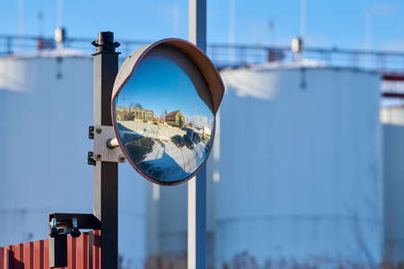 Mirror of spherical type on telegraph pole reflecting road. Large convex mirror on road for improving visibility. Convex mirror for roadside safety. Traffic curved glass.