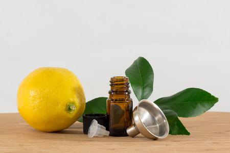 limonene: Lemon Essential Oil Bottle With Black Cap, Citrus Leaves and Funnel
