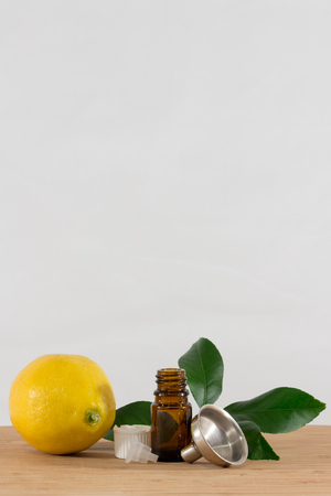 limonene: Lemon Essential Oil Bottle With White Cap, Citrus Leaves and Funnel