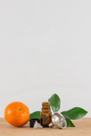 limonene: Orange Essential Oil Bottle With Black Cap, Citrus Leaves and Funnel