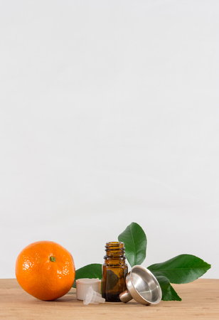 limonene: Orange Essential Oil Bottle With White Cap, Citrus Leaves and Funnel Stock Photo