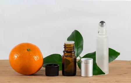 limonene: Orange Essential Oil Bottle With Black Cap, Citrus Leaves and Roller Bottle Stock Photo