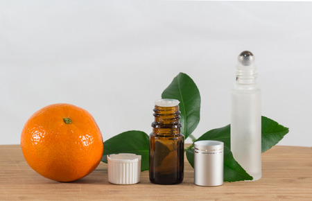 stimulate: Orange Essential Oil Bottle With White Cap, Citrus Leaves and Roller Bottle