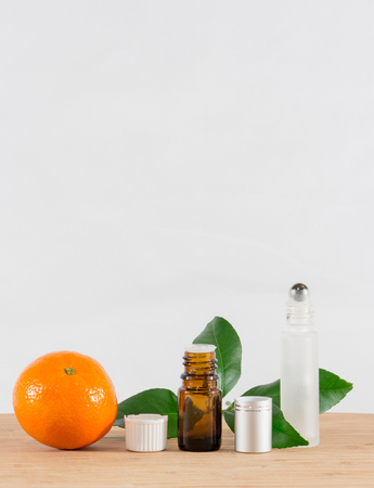 Orange Essential Oil Bottle With White Cap, Citrus Leaves and Roller Bottle Stock Photo - 56602411
