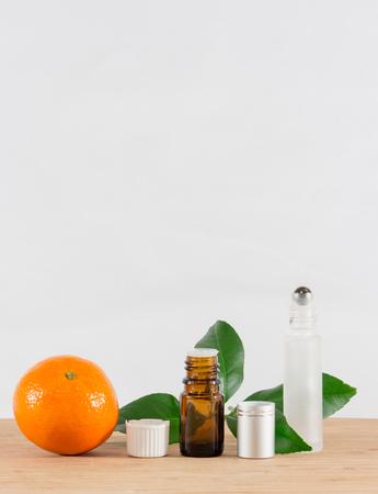 limonene: Orange Essential Oil Bottle With White Cap, Citrus Leaves and Roller Bottle