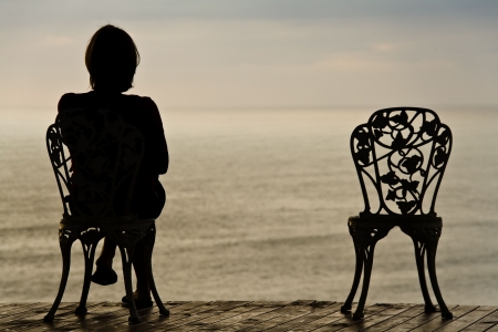 Lonely girl sitting on a vintage chair photo