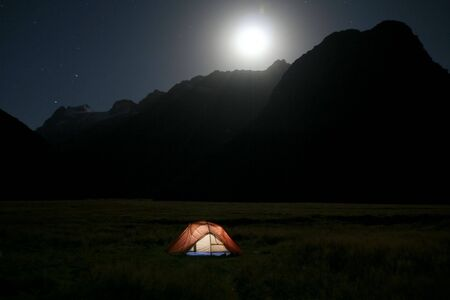 Moon rising over a tent in the wilderness
