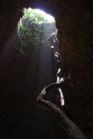 overhang: high hole in the roof of a cave and the only exit Stock Photo