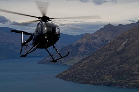 A Chopper circling over Queenstown, New Zealand Stock Photo