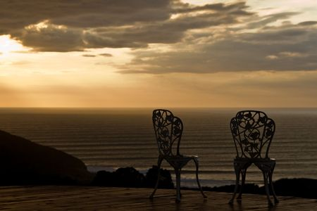 A couple of vintage chairs with a great sunset view photo