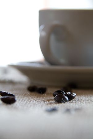 stylish coffee mug with beans in the foreground Stock Photo