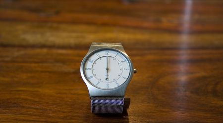mans wristwatch on a wooden counter showing 6 oclock