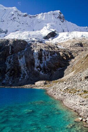 mountain lake panorama with blue water and reflecting sun