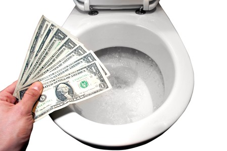 hand with dollar notes over a flushing toilet, isolated photo