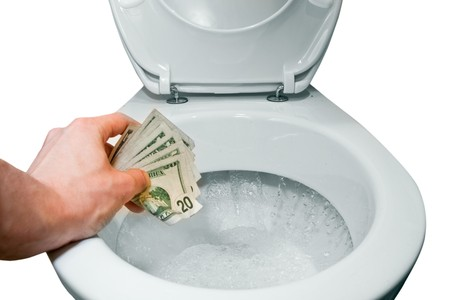 mans hand flushing some dollars, isolated on white
