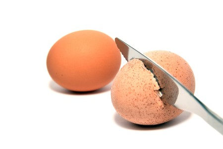knife while cutting a breakfast egg isolated on white photo