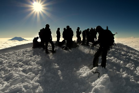 a number of silhouettes standing on the peak of cotopaxi, an ice packed mountain
