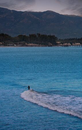 longboard surfer in santa cruz, california from the distance