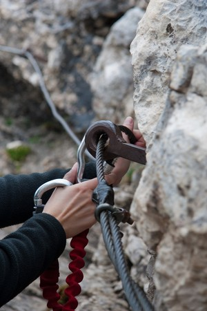 female hands caring for safety with a carabiner while climbing photo