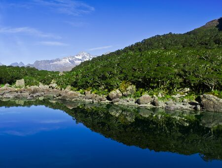 cold, clear, blue lake in the mountains with nice reflections and trees Stock Photo