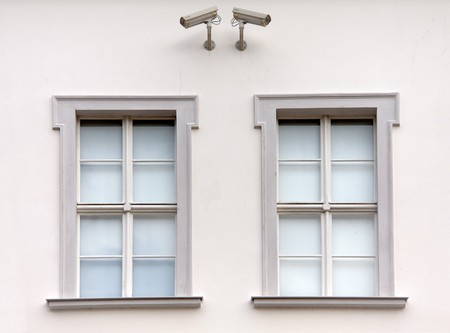 two cameras on a house wall controlling two windows