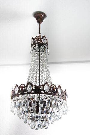 Candelabro elegante con cristales colgado en una habitación blanca  Foto de archivo