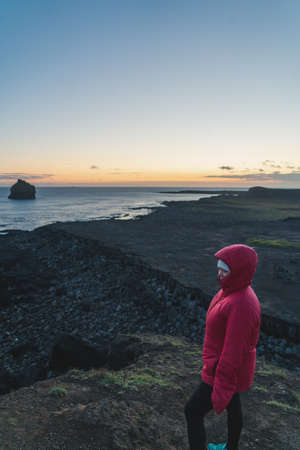 a woman wearing a red jacket stands by the edge of a small cliff at sunset
