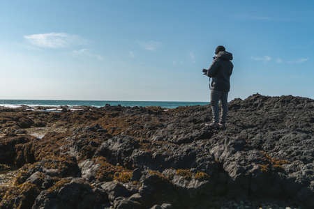 a man admires the uncovered rocks by the low tide in Selatangar.