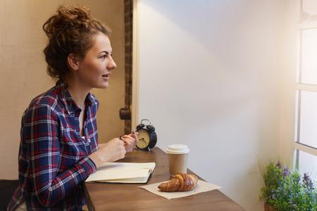 De jonge charmante vrouwelijke student met krullend haar maakt nota's, hebbend ontbijt met koffie en croissant bekijkend het venster en denkend over plannen voor nieuwe dag Stockfoto