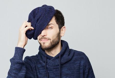 Headshot van modieuze jonge blauw-eyed bearded man met baard afnemen stijlvolle hoed winks op de camera.Face emotie concept. Stockfoto