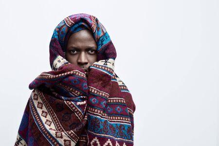 Uitingen en emoties van het menselijke gezicht. Close-up portret van ongelukkig, bang, angstig bezorgd, verlangen naar iets African American man kijken naar de camera, bedekt met etnische deken. Geïsoleerd op witte achtergrond