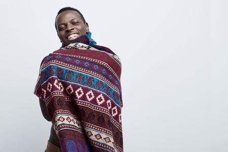 Portrrait van vertrouwen jonge donkere man standing geïsoleerd tegen grijze studio muur achtergrond met kopie ruimte voor uw tekst of promotionele inhoud, met vriendelijke vrolijke gezicht expressie. Stockfoto