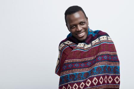Hoofd geschoten portret van jonge gelukkig Afro-Amerikaanse man, op zoek vriendelijk, lacht of lacht naar de camera. Bedekt met etnische deken en bewegen op een grijze achtergrond Stockfoto
