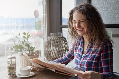 Aantrekkelijke jonge internationale student die een ochtend krant zit in de straat cafe en heerlijke groene thee drinken. Lachende hipster meisje leest grappig artikel tijdens het ontbijt