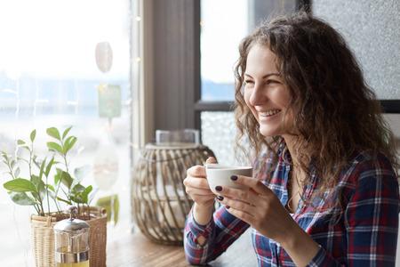 De jonge vrij vrouwelijke student drinkt haar groene thee in moderne koffie die goede stemming en het glimlachen hebben opzij kijkend om ruimtegebied voor uw reclameberichten of inhoud te kopiëren