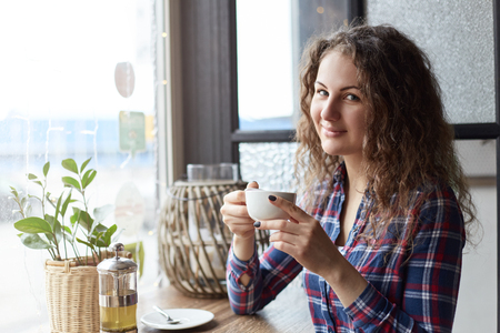 Het vrij jonge blauw-eyed meisje zit in modern koffie met een kop van groene organische thee wachtend op haar lunch en glimlachend bij de camera. Er is een kopieergebied voor uw reclameboodschappen of inhoud