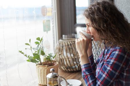 Sluit omhoog portret van aantrekkelijke Kaukasische dame die een slokje van thee in moderne koffiewinkel nemen die het venster bekijken die op vrienden wachten die zitting dichtbij exemplaar ruimtegebied voor uw reclameberichten of inhoud ontmoeten Stockfoto