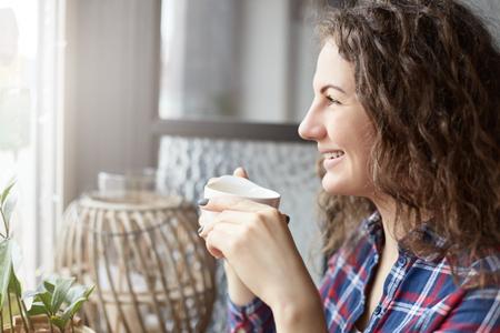 Sluit omhoog portret van aantrekkelijke vrouwelijke internationale student die rust hebben tijdens onderbreking in koffiewinkel die op vrienden wachten die vergadering dichtbij exemplaar ruimtegebied voor uw reclameberichten of inhoud ontmoeten Stockfoto