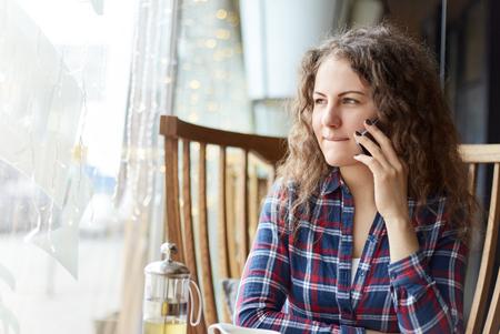 Jonge charmante vrouw die mobiele telefoon belt tijdens de vrije tijd alleen in de koffiewinkel zitten. Twijfelachtig en onbeslisend, ze kijkt naar het raam met doordachte nadenkende uitdrukking, achtervolgend haar lippen, wachtend op haar lunch klaar te zijn.