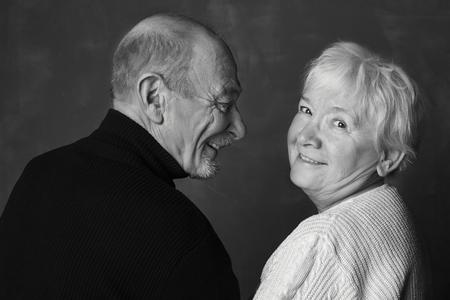 Zwart en wit studio shot van ouder wordende paar met plezier en gezegend met liefde. Tijdens de liefde kijkt de dansende mens naar zijn partner en glimlacht zij naar de camera. Liefde en familie concept. Stockfoto