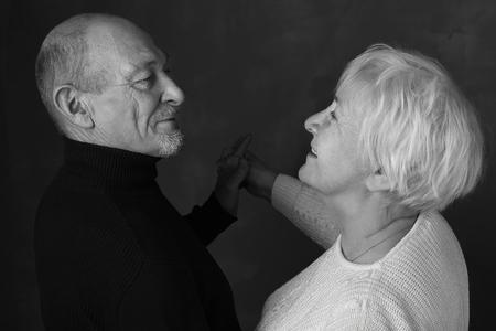 Portret van eindeloze liefde. Zwart en wit portret van gelukkig hoger paar die elkaar bekijken en glimlachen terwijl binnen status hand aan hand op een donkere achtergrond Stockfoto