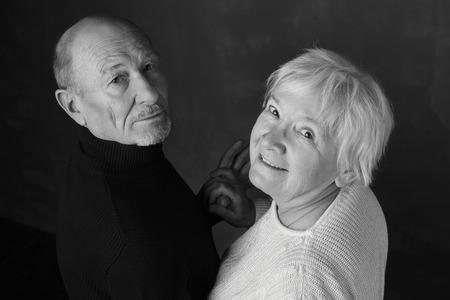 Zwart en wit portret van elegant hoger paar. De man en zijn vrouw dansen binnenshuis op donkergrijs en dragen de hand met de hand diep aan de camera. Liefde en familie concept