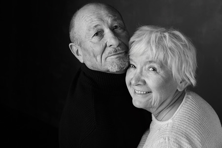 When two become one. The head studio shot of senior couple, looking and smiling at the camera. Black and white image with copy space area for your advertising messages or content on dark background