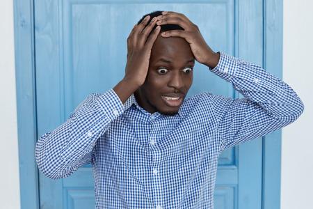 De grappige jonge Afro-Amerikaanse man met grote ogen in een geruit overhemd heeft een gekke blik en wenkbrauwen. Onthoud een belangrijke vergadering die hij heeft gemist vanwege een slecht geheugen of overbelasting. Stockfoto
